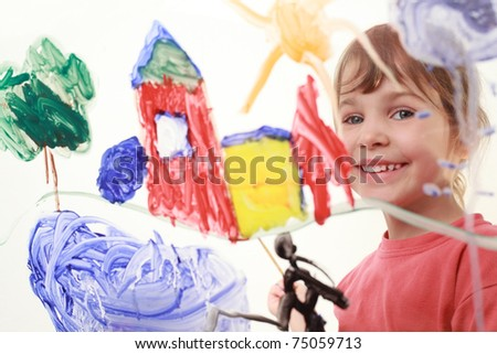 beautiful little girl in red t-shirt paints on glass and smiles, house, tree, sun