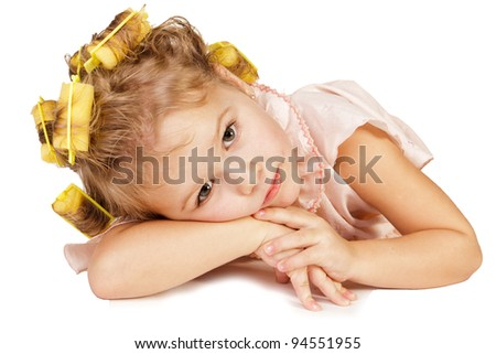 Beautiful little girl in rollers over white background