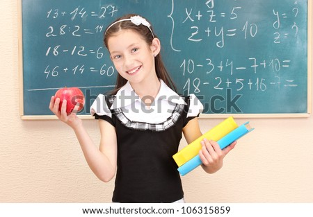 beautiful little girl in school uniform with books and apple in class room