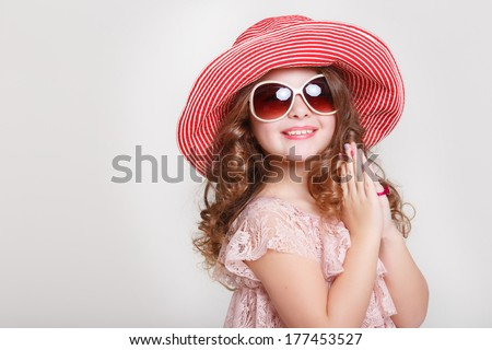 Beautiful little girl in summer hat and sunglasses on white background, portrait of cute happy child baby girl in lace princess dress in studio. kid summer fashion. isolated.