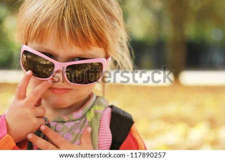 beautiful little girl in sunglasses in the autumn forest