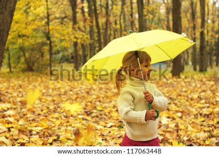beautiful little girl in the autumn forest with umbrella