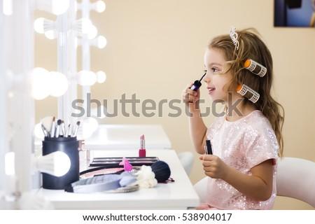 beautiful little girl in the mirror preening. little beauty stock photo