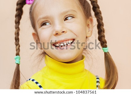 Beautiful little girl in yellow dress with pigtails looks askance, and laughing merrily.