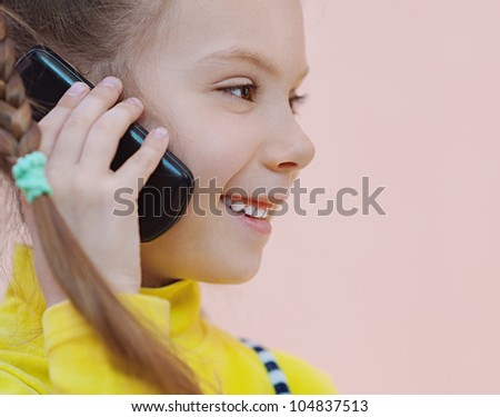 Beautiful little girl in yellow dress with pigtails talking on cell phone.