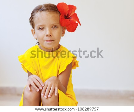 Dress on Beautiful Little Girl In Yellow Dress With Red Flower Sits On Stone