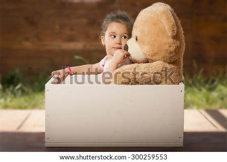 Beautiful little girl inside white wooden box with toy bear pretending to be in a car. Little girl having fun playing