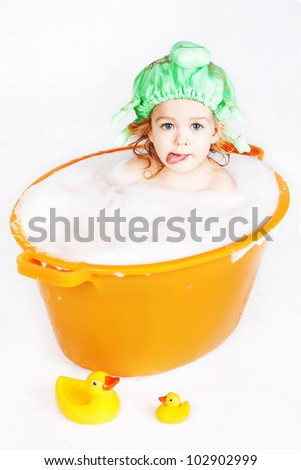 beautiful little girl is bathed in a red bowl with yellow ducks