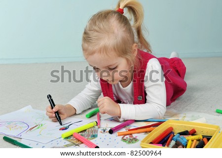Beautiful little girl is drawing  on paper
