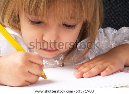 Beautiful little girl is drawing with pencil on paper