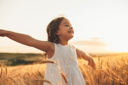 Beautiful little girl laughing and running with hand up in a wheat field against sunset. Freedom concept.