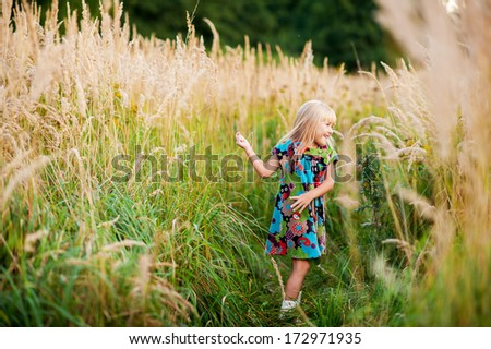 beautiful little girl laughs and rotates outdoors in a meadow during sunset