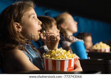 Beautiful little girl looking fascinated eating popcorn watching a movie at the local movie theatre snack bucket junk food tasty childhood entertaining entertained emotions kids concept #773743066