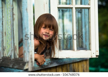 Beautiful little girl looks out the window rural house stock photo
