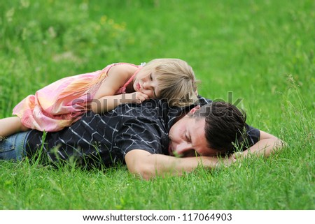 beautiful little girl lying on her father in nature
