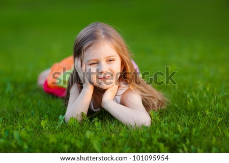 Beautiful little girl lying on the grass in summer park