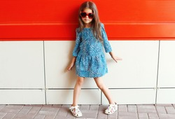 Beautiful little girl model wearing a leopard dress and sunglasses over colorful red background