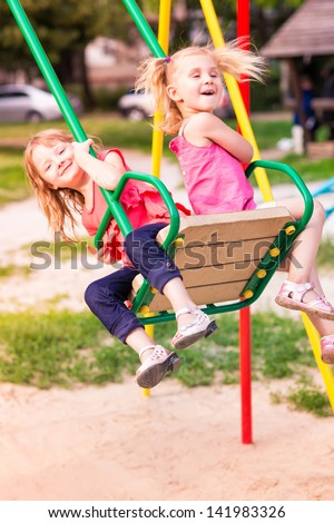 Beautiful little girl on a swings outdoor in the playground at summertime