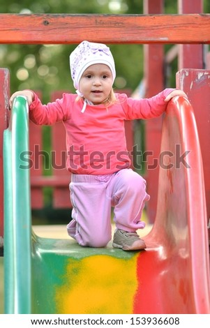 Beautiful little girl on outdoor playground at summertime