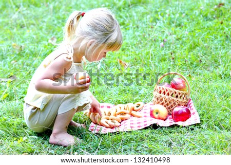 beautiful little girl outdoors with apple