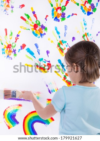 Beautiful little girl painting over white #179921627