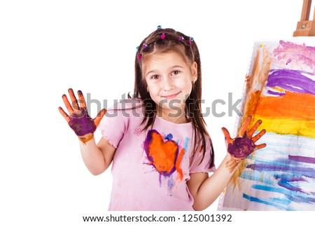 Beautiful little girl painting with her hands over white background