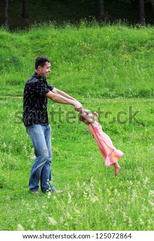 beautiful little girl play with dad in nature