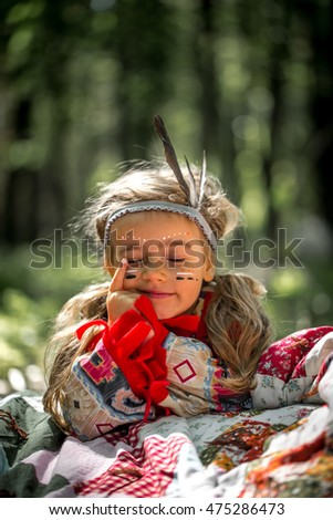 beautiful little girl playing outdoors in the image of the Indian, the emotions of a little girl