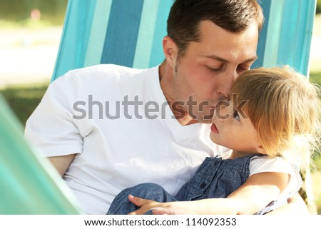 Beautiful little girl playing with her father in nature