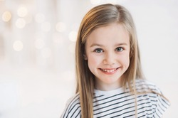 Beautiful little girl portrait at home. Cute child smiling and looking at camera