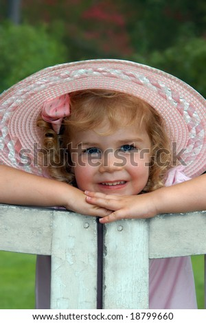Beautiful little girl poses on a garden gate.  She is wearing a pink, hat, bow and dress.
