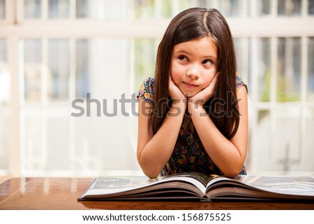 Beautiful little girl reading and daydreaming in the living room