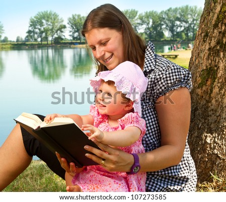 beautiful little girl reading book with her mother