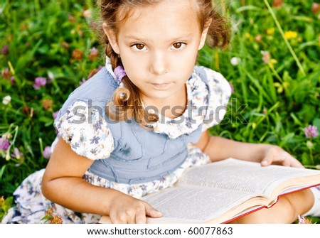 Beautiful little girl reads book, sitting on green lawn.