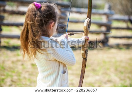 Beautiful little girl shoots bow at entertainment park.