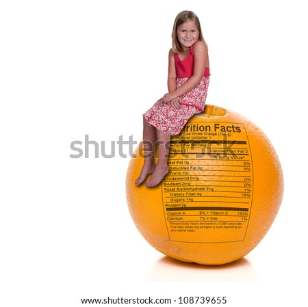 Beautiful little girl sitting on an orange with a nutrition label
