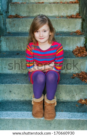 Beautiful little girl sitting on steps outdoors, wearing colorful dress