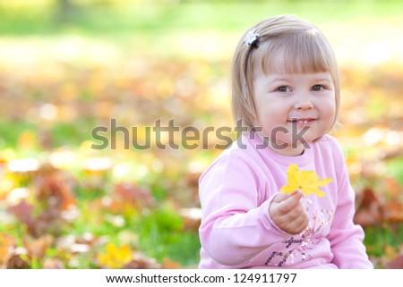 beautiful little girl sitting on the autumn leaves