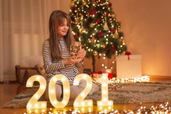 Beautiful little girl sitting on the floor by nicely decorated Christmas tree, arranging illuminated numbers 2021 representing the upcoming New Year, decorating home for winter holidays