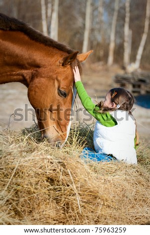 Beautiful little girl sitting on the hay, which eats the horse and flatter it. True Friendship.