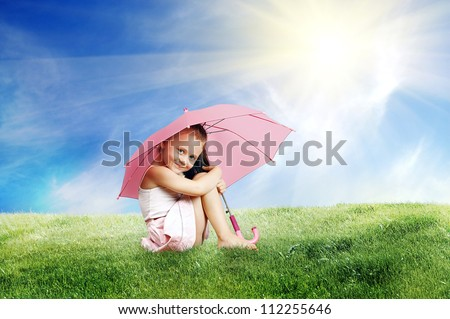 Beautiful little girl sitting under an umbrella on the lawn