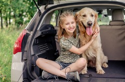 Beautiful little girl sitting with golden retriever dog in the car trunk and smiling looking at the camera. Child kid hugging purebred doggy pet in the vehicle at the nature