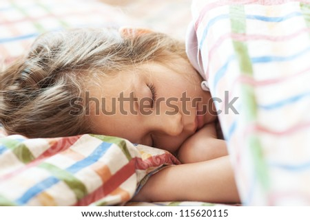 Beautiful little girl sleeping in bed close-up.
