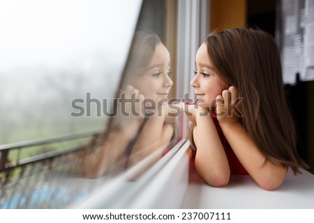 Beautiful little girl smiling and watching out the window. A child looks out the window. Young girl looking from window. Portrait of cheerful kid lies at windowsill. #237007111