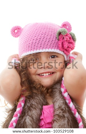 beautiful little girl smiling in knitted hat.