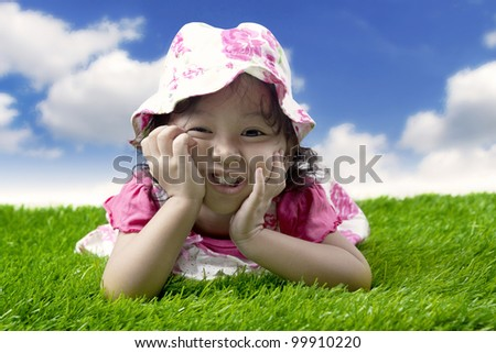 Beautiful little girl smiling in the green grass. Shot outdoor on the meadow