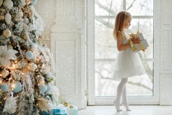 Beautiful little girl standing on tiptoes at the large window and holding a gift, in the bright New Year's interior