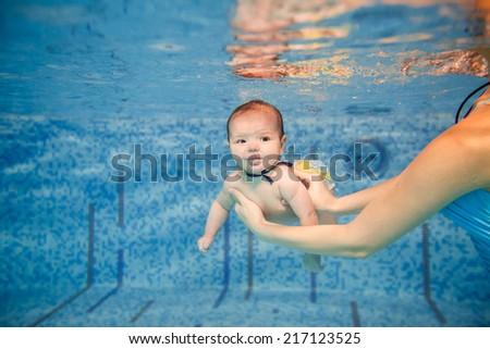 beautiful little girl swims underwater. child development, disease prevention