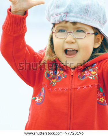 Beautiful little girl wearing glasses 3 years old in denim jeans cap and red jacket