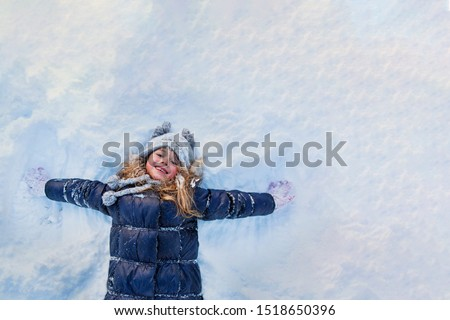 Beautiful little girl wearing navy jacket and knitted hat playing in a snowy winter park. Child playing with snow in winter. Kid play and jump in snowy forest. Family vacation with child in mountains